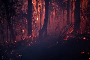 A bushfire burns close to homes on Railway Parade in Woodford, NSW