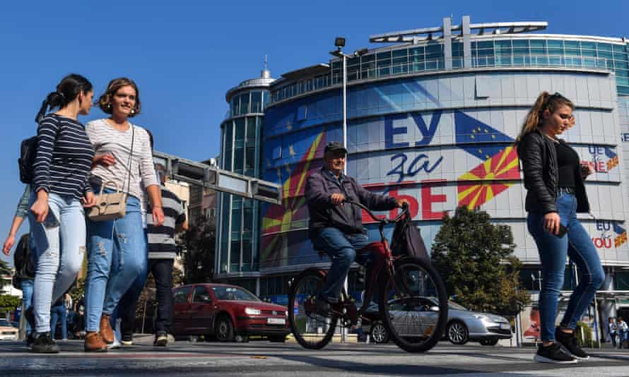 People in Skopje, North Macedonia, walk past the offices of the European Union with logos reading 'EU for You'