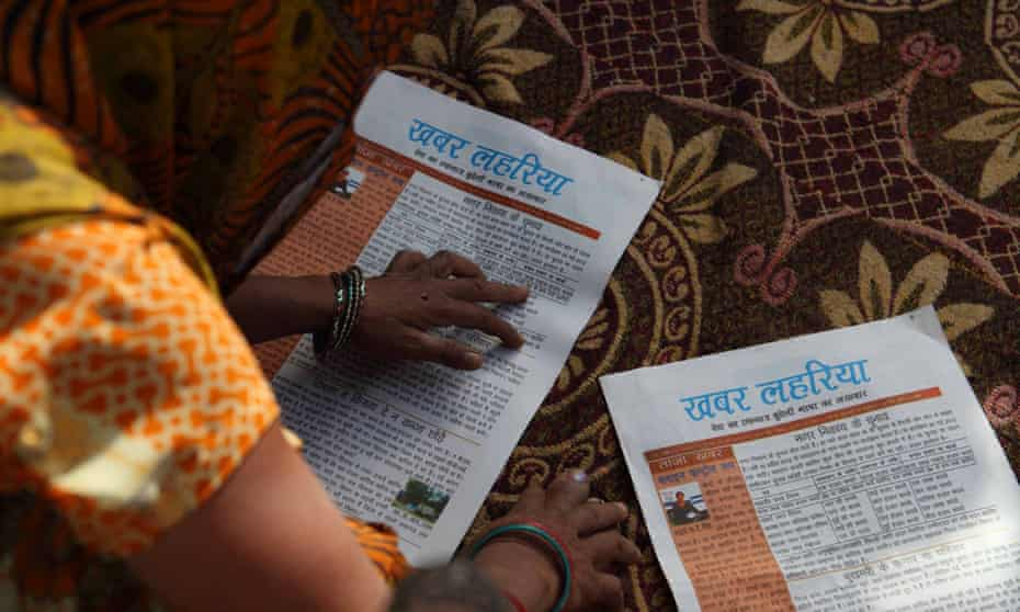 Staff pore over an edition of Khabar Lahariya (Waves of News), which is edited entirely by women.