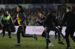 Newport County fans rush onto the pitch after the final whistle goes.