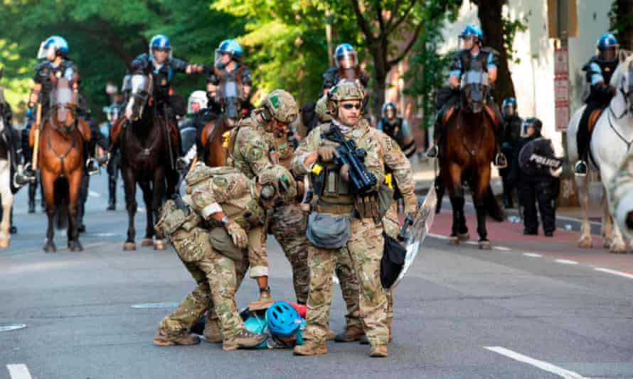 Military police officers are restraining a protester near the White House on Monday.