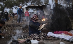 A woman makes bread at a an overcrowded refugee camp on Lesbos