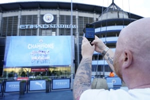A Manchester City fan takes a photo of the unfurled banner as he celebrates the club's title victory outside the Etihad.