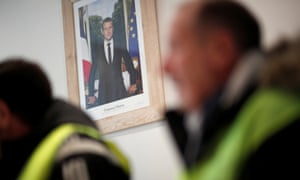 The official portrait of French President Emmanuel Macron is seen during a meeting with yellow vests movement members