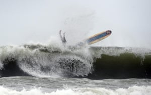 A surfer gets wiped out by the big seas in Mooloolaba on the Sunshine Coast.