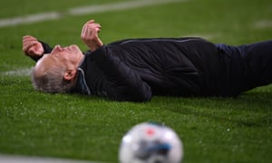 Freiburg's coach, Christian Streich, lies on the turf after being knocked over by David Abraham of Eintracht Frankfurt.
