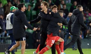 Julen Lopetegui (centre) celebrates with his Sevilla team after their derby victory at Real Betis.