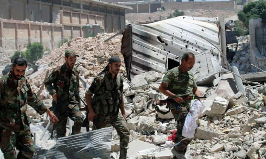 Forces loyal to President Assad walk past rubble in Aleppo
