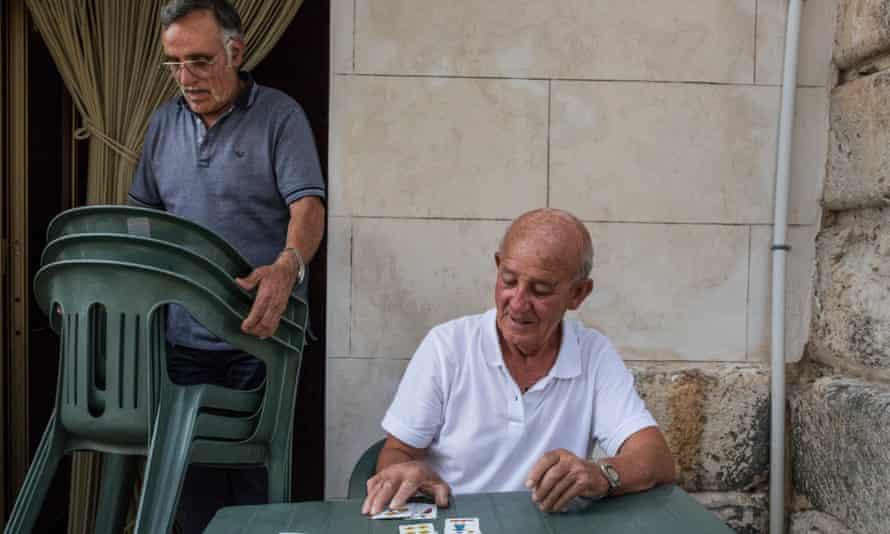 Giuseppe Li Pani 81, enjoys playing cards in Acquaviva Platani's Piazza Plado Mosca.