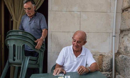 Giuseppe Li Pani 81, enjoys playing cards in Acquaviva Platani's Piazza Plado Mosca.