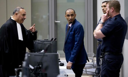 Al Hassan listens as his duty counsel, Yasser Hassan, talks to security guards.