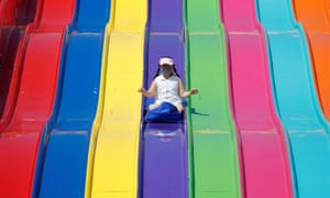 A young girl wearing a mask slides down on a ride as the Calgary Stampede gets underway following a year off due to COVID-19 restrictions, in Calgary, Alberta, Canada.