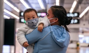 A woman carries a baby wearing a protective mask as they exit the arrival hall at Hong Kong High Speed Rail Station on 29 January 2020 in Hong Kong, China.