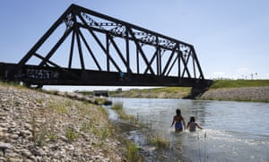 Young people try to beat the heat in an irrigation canal in Chestermere, Alberta