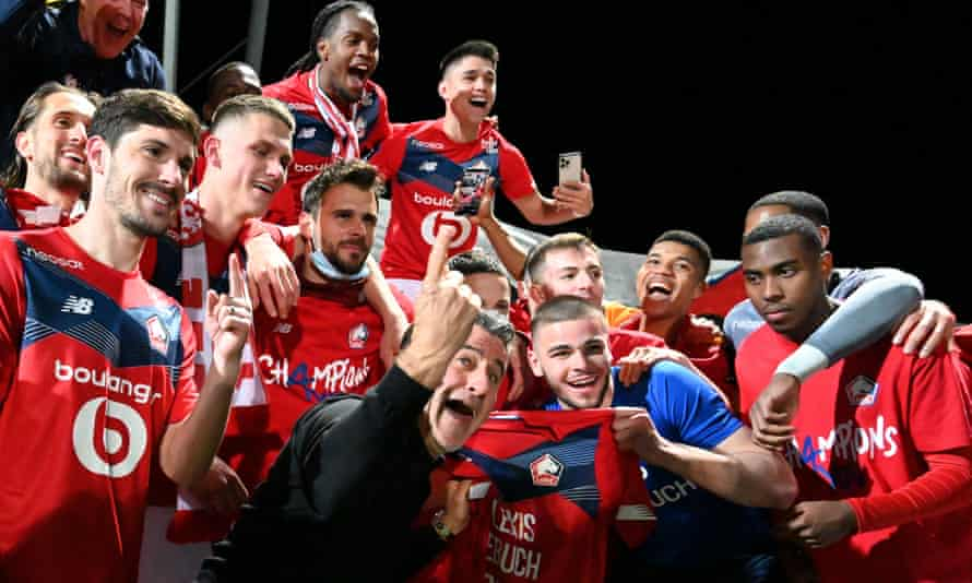Lille coach Christophe Galtier celebrates the title with his players.