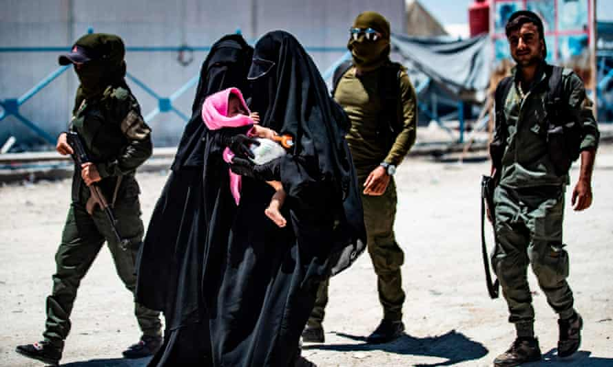 An internal security patrol escorts women, reportedly wives of Isis fighters, in the al-Hawl camp in north-east Syria.