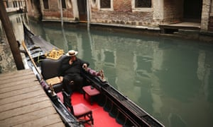 A gondolier talks on his smartphone as he waits for clients in Venice.