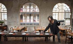 A waitress laying a table in Casa do Frango's dining room with three floor to ceiling arched windows in the background