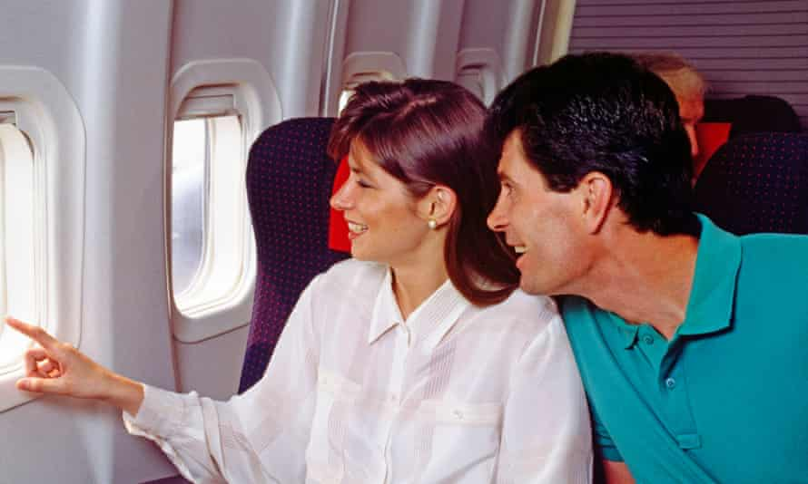 A couple wearing 1990s fashion stare out the window of an aeroplane