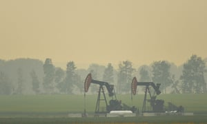 A view of an extraction pump for oil and gas on a field near the town of Sundre, Alberta, Canada, during smoky and hazy weather conditions impacted by wildfire smoke.