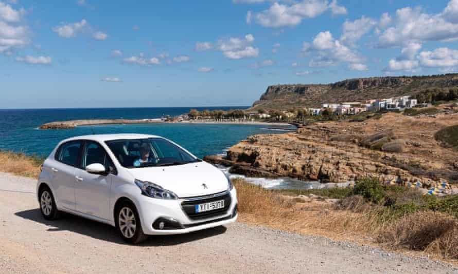 Driving a rental car along a coast road overlooking Sissi beach near Malia, Crete.