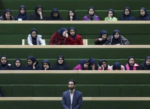 A security guard stands by while Iranian school girls attend an open session of parliament in Tehran.