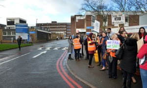 Demonstrators hold placards on the picket line outside Sandwell hospital.
