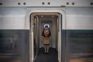 A train attendant wearing a protective face mask stands on a train to Wuhan.