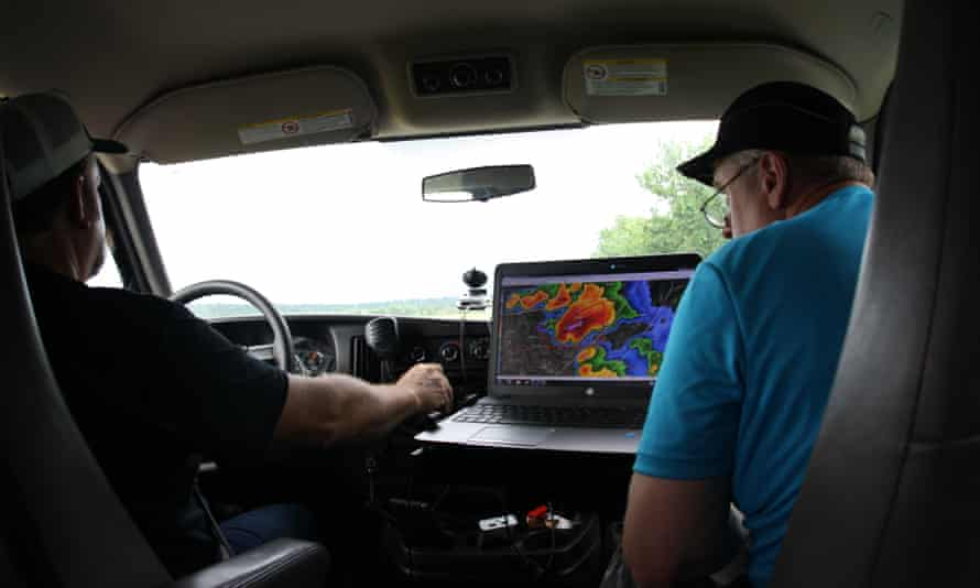 Stormchasers check weather details on a laptop while sat in a van. Oklahoma, US.
