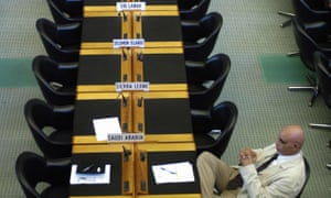 A lone WTO official sits at a long table with empty chairs