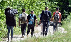 A group of migrants walk through countryside in northern Bosnia after being physically expelled by police from Croatia.