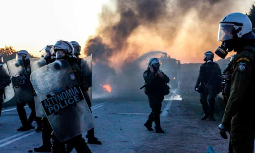Riot police walk on a road near the town of Madamados on the north-east Aegean island of Lesbos.