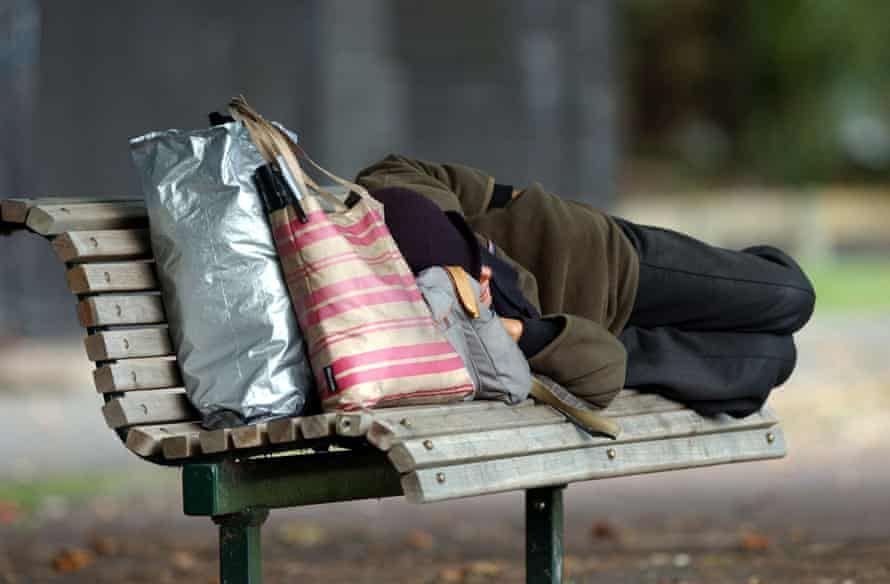 A homeless person on a park bench in Victoria Park