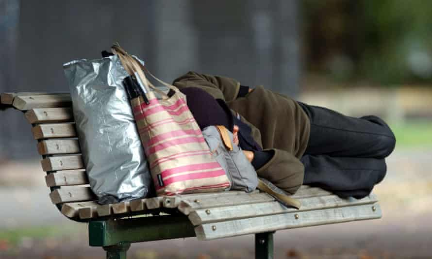 Homeless person sleeping on a park bench in auckland, new zealand