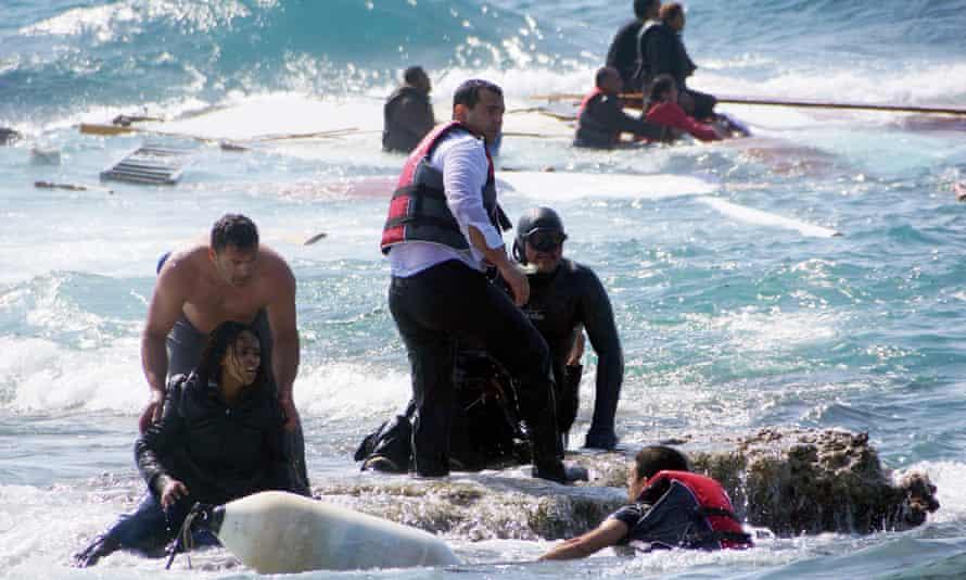 Greek islander Antonis Deligiorgis, left, pulls an Eritrean woman, Wegasi Nebiat, from the sea off Rhodes last year.