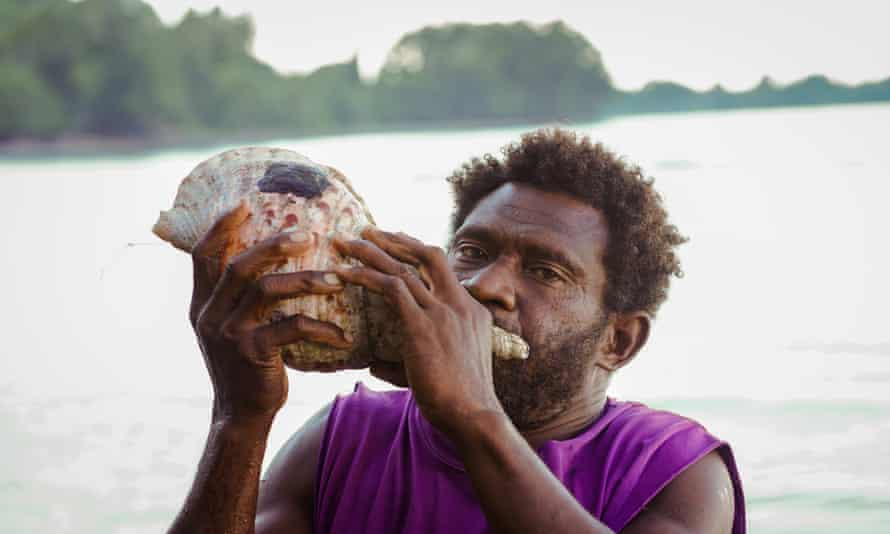 Amos Lavaka blowing a conch shell at Messi village
