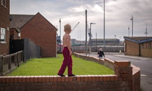A boy with no top on stands on a garden wall in Hartlepool.
