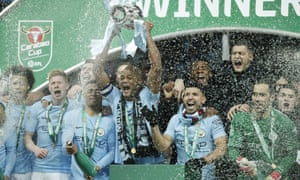 Vincent Kompany lifts the Carabao Cup trophy as Manchester City players spray champagne.