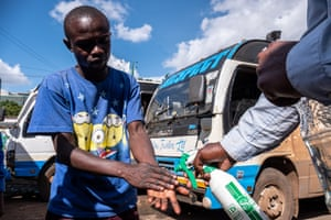 Before people can enter the matatu buses of Nairobi, their hands are disinfected by staff
