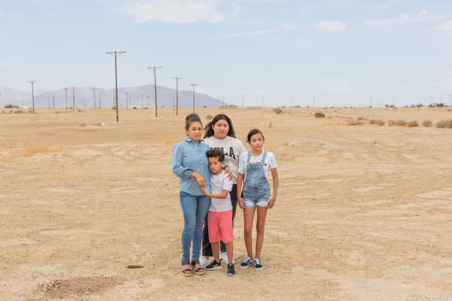 Miriam Juárez stands with her two daughters, her arm around her son on a dusty expanse.