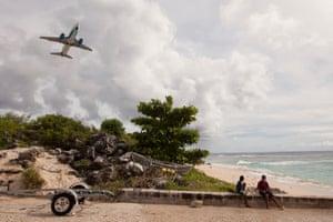 Two local Nauruan boys watch a plane take off.