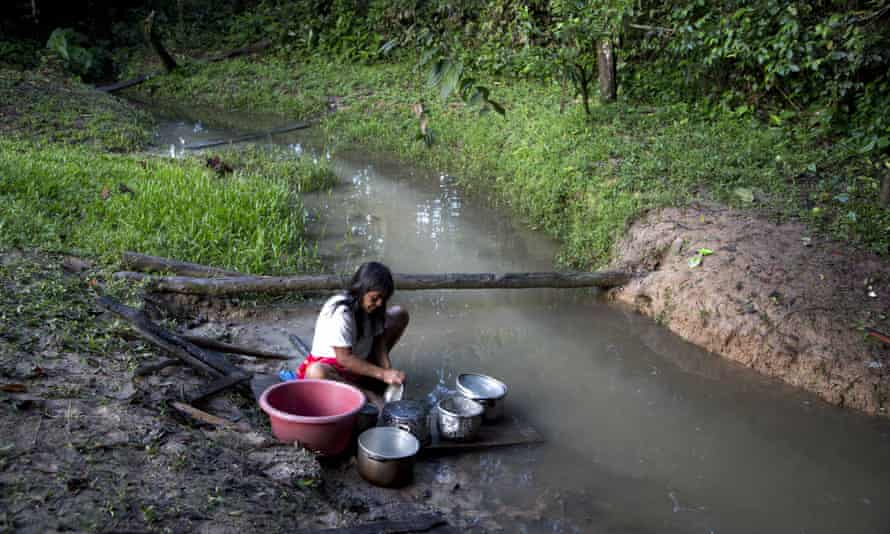 Ashaninka Teresa Lopez washes pots after cooking breakfast for her family, along a stream in the hamlet of Saweto, Peru.