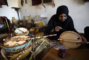 Cheynoune Zeineb, a Tuareg and imzad instrument maker, sits crossed legged while decorating an imzad with personalised Tuareg motifs