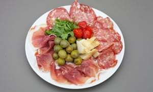A round white plate of Parma ham and peppercorn salami, with artichoke heart, olives, and rocket in the centre