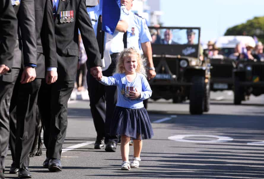 A young girl is seen wearing medals during an Anzac Day march in Southport on the Gold Coast , Tuesday, April 25, 2017