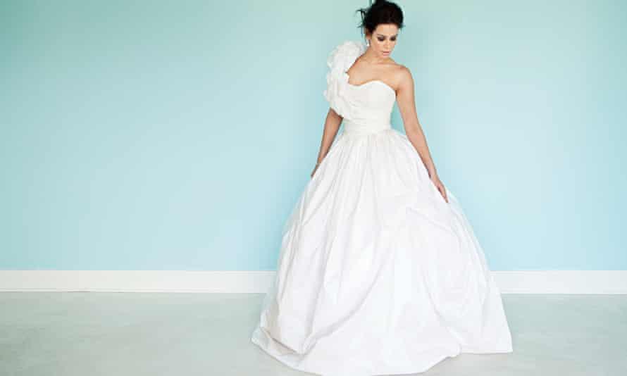 Young woman wearing white wedding dress, studio shot
