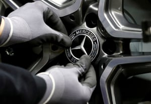 An employee of German car manufacturer Mercedes Benz installs a hubcap at a A-class model at the production line at the Daimler factory in Rastatt, Germany.
