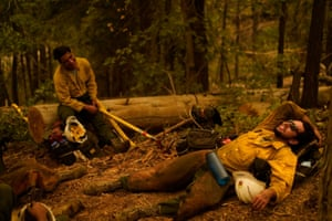 Firefighters rest after a night battling the Creek fire
