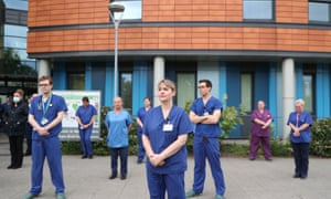 Staff stand outside Salford Royal Hospital in Manchester observing the minute's silence.