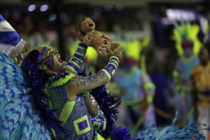 A performer from the Portela samba school lifts a mannequin of a newborn baby during the parade